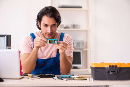 Young male contractor repairing computer Stockfoto