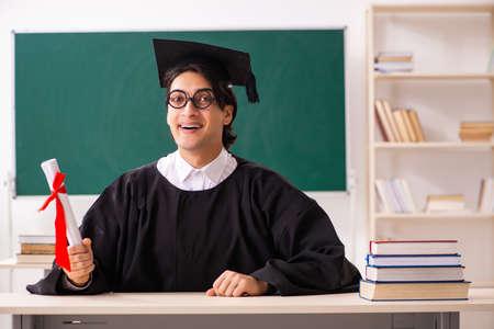 Estudiante graduado frente a tablero verde