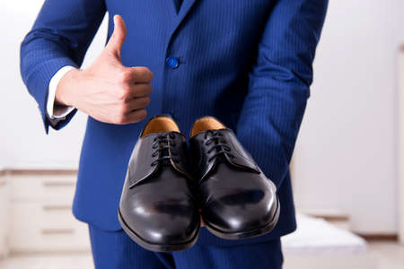 Young handsome businessman choosing shoes at home Stock Photo