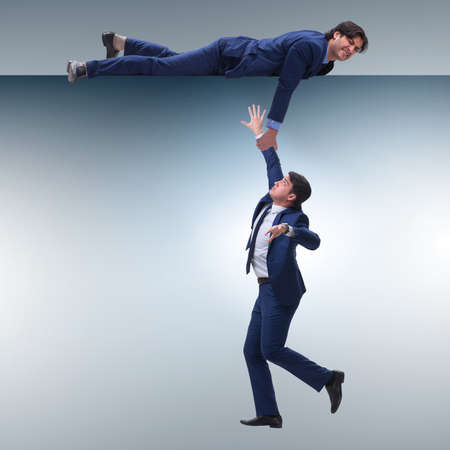 Businessman offering helping hand to falling colleague
