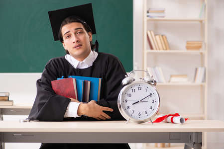 Graduate student in front of green board Standard-Bild
