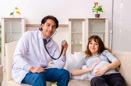 Joven apuesto médico visitando a la mujer embarazada en casa