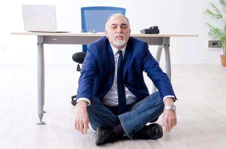 Aged businessman doing yoga exercises in the office