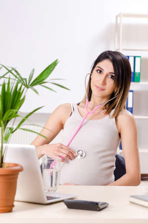Young pregnant employee working in the office