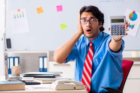 Junger männlicher Finanzmanager, der im Büro arbeitet