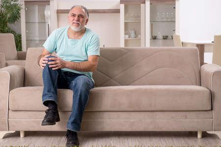 Witte bebaarde oude man die thuis lijdt