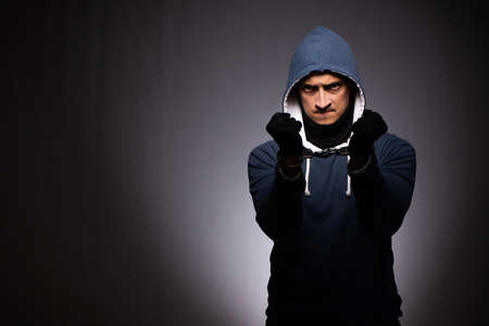 Young gangster in hood on grey background Stock Photo