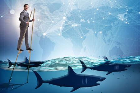 Homme d'affaires marchant sur des échasses parmi les requins