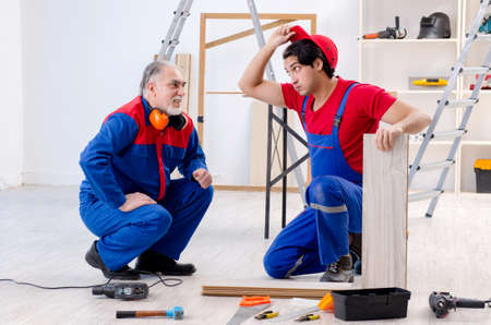 Two professional contractors laying flooring at home