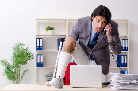 Leg injured employee working in the office 스톡 콘텐츠