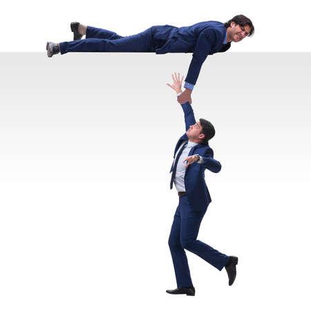 Zakenman die helpende hand aanbiedt aan vallende collega Stockfoto