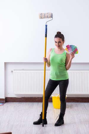 Young beautiful woman doing renovation at home Imagens