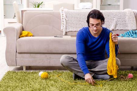 Junger gutaussehender Mann, der zu Hause strickt