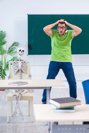 Funny male student in the classroom with skeleton
