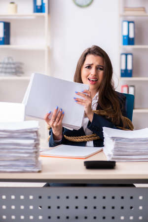 Young beautiful employee tied up with rope in the office Stock Photo