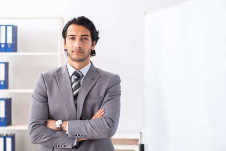 Young handsome businessman in front of whiteboard Banco de Imagens