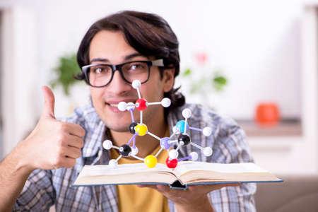 Junger Physikstudent, der sich zu Hause auf die Prüfung vorbereitet Standard-Bild