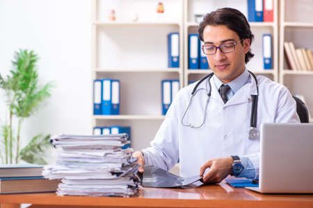 Young handsome doctor working in the clinic Stock Photo