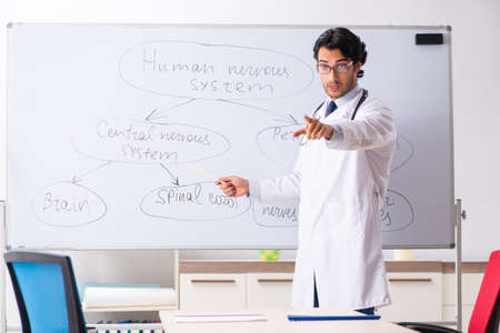 Young male doctor neurologist in front of whiteboard Foto de archivo