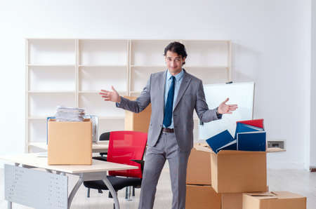 Young man employee with boxes in the office