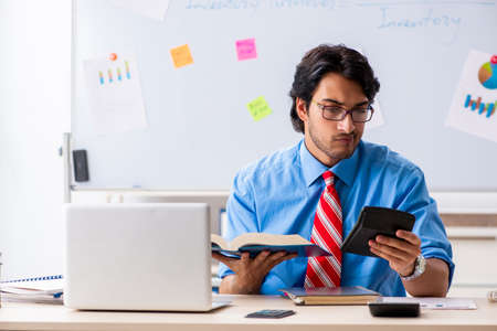 Young male financial manager working in the office Imagens