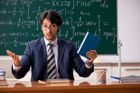 Young male math teacher in classroom Imagens