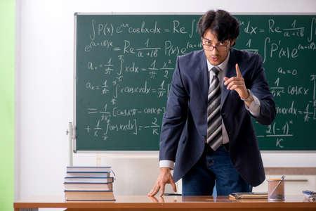 Young male math teacher in classroom 版權商用圖片