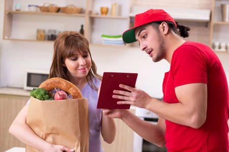 Young male courier in food delivery concept