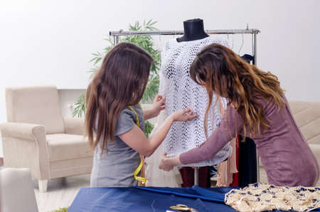 Young beautiful female tailor taking measurements Фото со стока