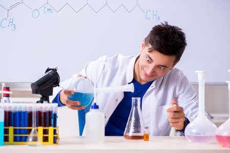 Young chemist sitting in the lab