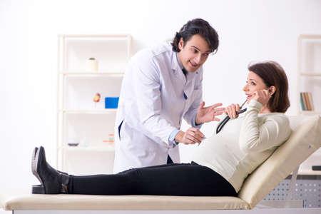 Vecchia donna incinta che visita un giovane dottore maschio male