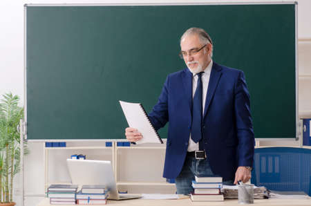 Aged male teacher in front of chalkboard