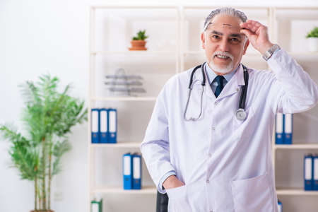 Aged male doctor working in the clinic Stock fotó
