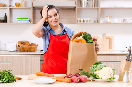 Mujer joven con verduras en la cocina