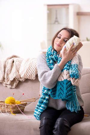 Jeune belle femme tricotant à la maison