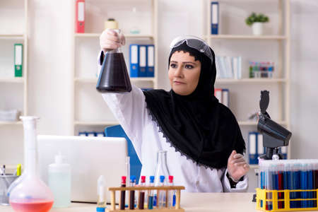 Chimiste féminin en hijab travaillant dans le laboratoire
