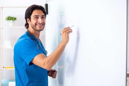Junger männlicher Arzt vor Whiteboard Standard-Bild