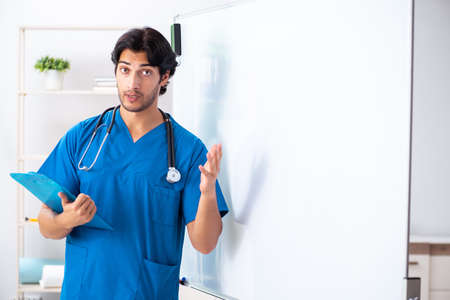 Young male doctor in front of whiteboard Banque d'images