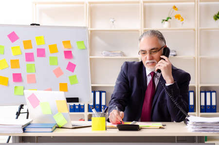 Aged man employee in conflicting priorities concept