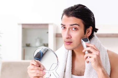 Junger gutaussehender Mann im Badezimmer