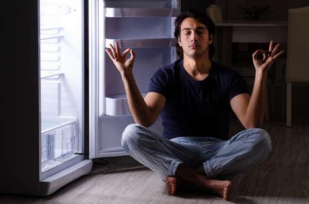 Homme cassant le régime la nuit près du réfrigérateur