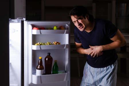 Man breaking diet at night near fridge Фото со стока