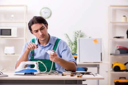 Young man repairing iron in service centre