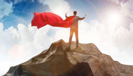 Superhero businessman on top of mountain