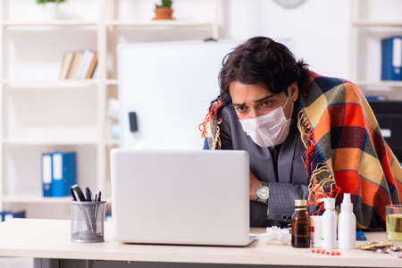 Man with flu working in the office Foto de archivo