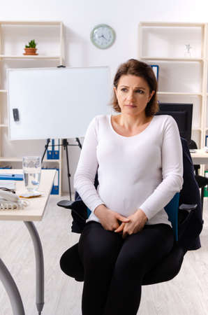 Old pregnant woman working in the office