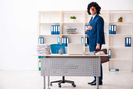 Young clown businessman working in the office