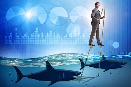 Businessman walking on stilts among sharks