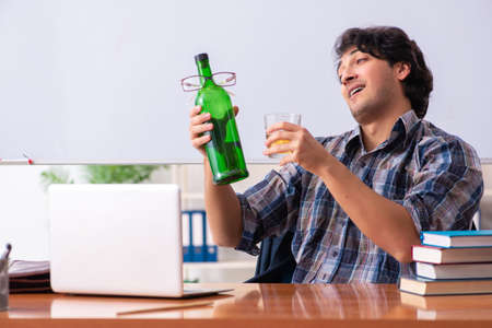 Male teacher drinking in the classroom