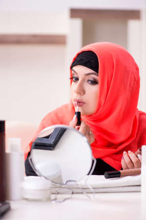 Beautiful woman in hijab applying make-up